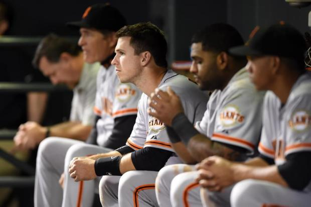 Apr 22, 2014; Denver, CO, USA; San Francisco Giants catcher Buster Posey (28) and teammates watch from the dugout in the ninth inning against the Colorado Rockies at Coors Field. The Rockies won 2-1. Mandatory Credit: Ron Chenoy-USA TODAY Sports