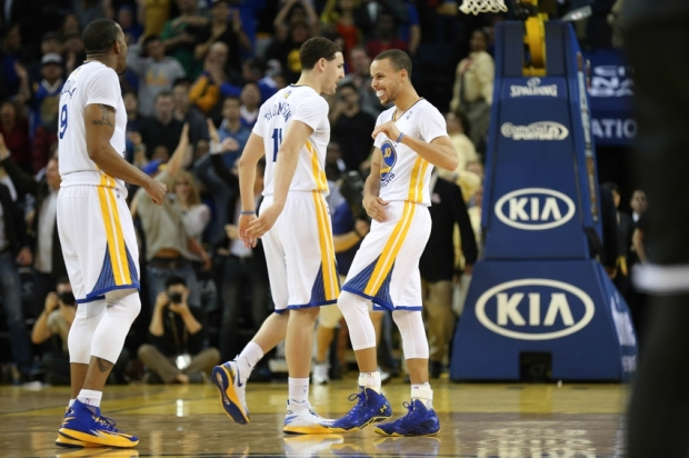 Feb 22, 2014; Oakland, CA, USA; Golden State Warriors point guard Stephen Curry (30) celebrates with shooting guard Klay Thompson (11) and small forward Andre Iguodala (9) after scoring a three point basket against the Brooklyn Nets during the fourth quarter at Oracle Arena. The Golden State Warriors defeated the Brooklyn Nets 93-86. Mandatory Credit: Kelley L Cox-USA TODAY Sports