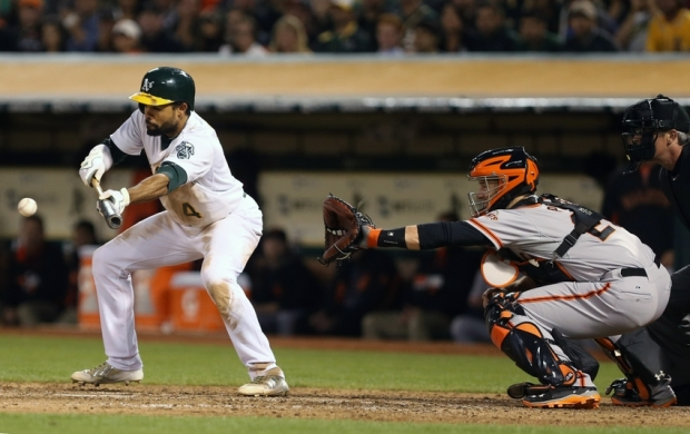 Jul 7, 2014; Oakland, CA, USA; Oakland Athletics center fielder Coco Crisp (4) reaches on a bunt single against the San Francisco Giants during the fifth inning at O.co Coliseum. Mandatory Credit: Kelley L Cox-USA TODAY Sports