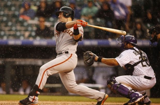 May 22, 2014; Denver, CO, USA; San Francisco Giants catcher Buster Posey (28) hits a single during the fifth inning against the Colorado Rockies at Coors Field. Mandatory Credit: Chris Humphreys-USA TODAY Sports
