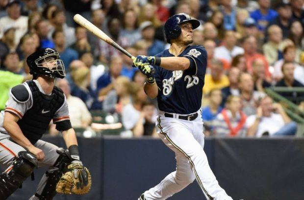 Aug 5, 2014; Milwaukee, WI, USA; Milwaukee Brewers right fielder Gerardo Parra (28) hits a solo home run in the seventh inning as San Francisco Giants catcher Andrew Susac (34) watches at Miller Park. Mandatory Credit: Benny Sieu-USA TODAY Sports