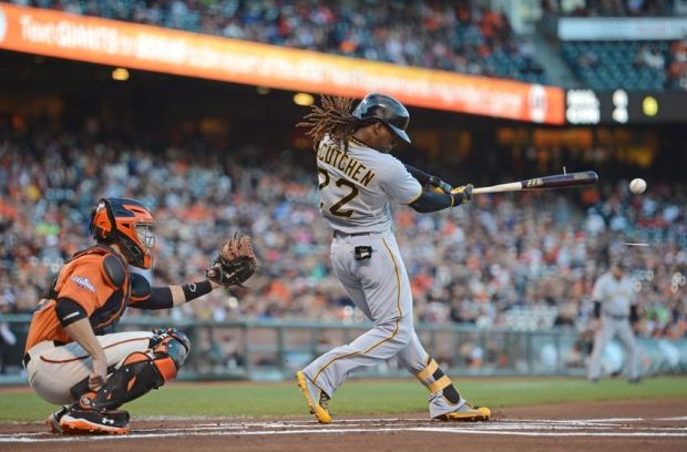 August 23, 2013; San Francisco, CA, USA; Pittsburgh Pirates center fielder Andrew McCutchen (22) hits a single in front of San Francisco Giants catcher Buster Posey (28, left) during the first inning at AT&T Park. Mandatory Credit: Kyle Terada-USA TODAY Sports