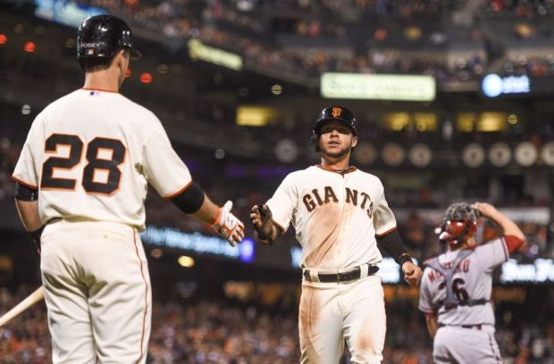 September 9, 2014; San Francisco, CA, USA; San Francisco Giants left fielder Gregor Blanco (7, center) is congratulated by first baseman Buster Posey (28) for scoring on a RBI-single by second baseman Joe Panik (12, not pictured) against Arizona Diamondbacks catcher Miguel Montero (26, right) during the sixth inning at AT&T Park. Mandatory Credit: Kyle Terada-USA TODAY Sports