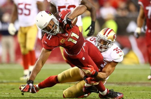 Dec 29, 2013; Phoenix, AZ, USA; Arizona Cardinals wide receiver Larry Fitzgerald (11) is tackled by San Francisco 49ers safety Eric Reid (35) in the fourth quarter at University of Phoenix Stadium. The 49ers defeated the Cardinals 23-20. Mandatory Credit: Mark J. Rebilas-USA TODAY Sports