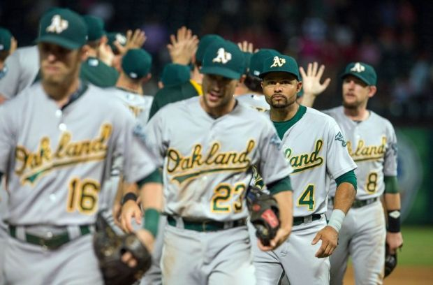 Sep 26, 2014; Arlington, TX, USA; The Oakland Athletics celebrate the win over the Texas Rangers at Globe Life Park in Arlington. The Athletics defeated the Rangers 6-2. Mandatory Credit: Jerome Miron-USA TODAY Sports