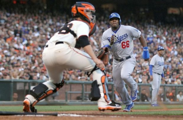Jul 26, 2014; San Francisco, CA, USA;  Los Angeles Dodgers center fielder Yasiel Puig (66) scores in front of San Francisco Giants catcher Buster Posey (28) in the sixth inning at AT&T Park. Mandatory Credit: Lance Iversen-USA TODAY Sports