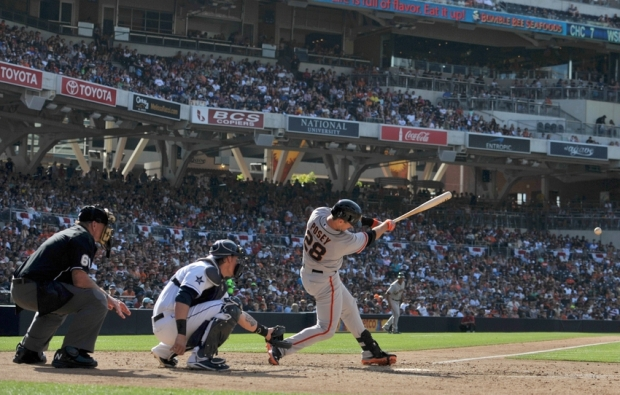 Jul 4, 2014; San Diego, CA, USA; San Francisco Giants catcher Buster Posey (28) singles during the sixth inning in front of San Diego Padres catcher Yasmani Grandal (middle) at Petco Park. Mandatory Credit: Jake Roth-USA TODAY Sports