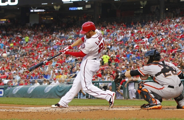 Aug 22, 2014; Washington, DC, USA; Washington Nationals first baseman Adam LaRoche (25) singles in front of San Francisco Giants catcher Buster Posey (28) in the first inning at Nationals Park. Mandatory Credit: Geoff Burke-USA TODAY Sports