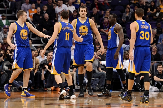 Dec 15, 2013; Phoenix, AZ, USA; Golden State Warriors center Andrew Bogut (12) in congratulated by teammates forward David Lee (10), guard Klay Thompson (11), forward Draymond Green (23) and guard Stephen Curry (30) in the second half of the game against the Phoenix Suns at US Airways Center. The Suns defeated the Warriors 106-102. Mandatory Credit: Jennifer Stewart-USA TODAY Sports