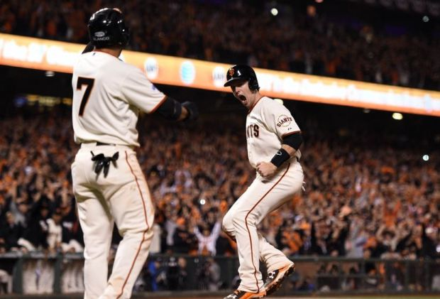 Oct 25, 2014; San Francisco, CA, USA; San Francisco Giants catcher Buster Posey (right) celebrates with center fielder Gregor Blanco (7) after both scoring runs against the Kansas City Royals in the sixth inning during game four of the 2014 World Series at AT&T Park. Mandatory Credit: Kyle Terada-USA TODAY Sports