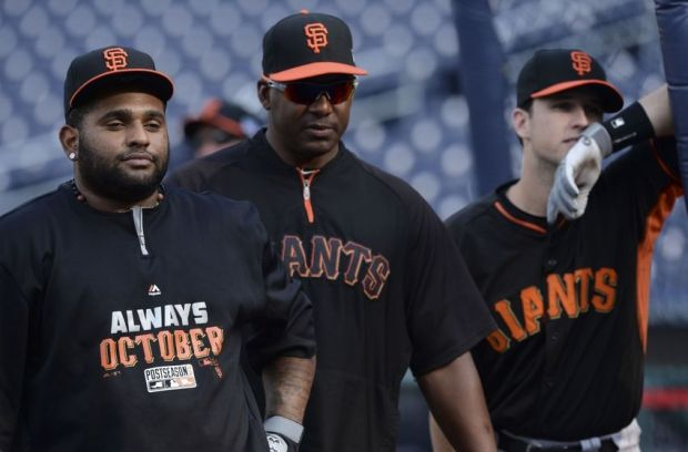 Oct 2, 2014; Washington, DC, USA; From left, San Francisco Giants third baseman Pablo Sandoval, batting coach Hensley Meulens and catcher Buster Posey pause during baseball workouts at Nationals Park. The Washington Nationals will play the San Francisco Giants Friday in Game 1 of the National League Division Series. Mandatory Credit: H.Darr Beiser-USA TODAY Sports