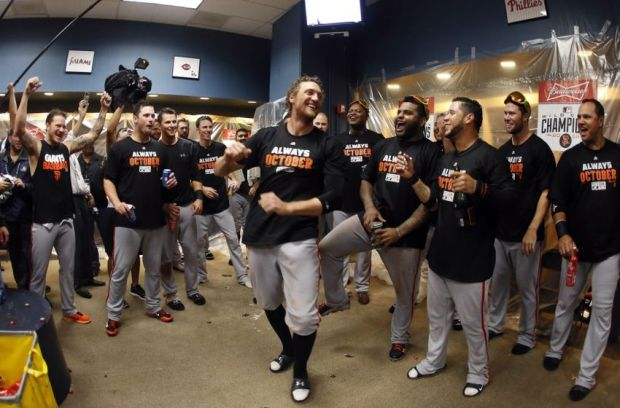 Oct 1, 2014; Pittsburgh, PA, USA; San Francisco Giants right fielder Hunter Pence (center) celebrates with teammates in the clubhouse after defeating the Pittsburgh Pirates in the 2014 National League Wild Card playoff baseball game at PNC Park. The Giants won 8-0. Mandatory Credit: Charles LeClaire-USA TODAY Sports