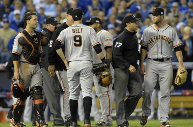 Oct 22, 2014; Kansas City, MO, USA; San Francisco Giants relief pitcher Hunter Strickland (right) is escorted away from home plate by umpire Jim Reynolds (77) in the sixth inning against the Kansas City Royals during game two of the 2014 World Series at Kauffman Stadium. Mandatory Credit: Christopher Hanewinckel-USA TODAY Sports