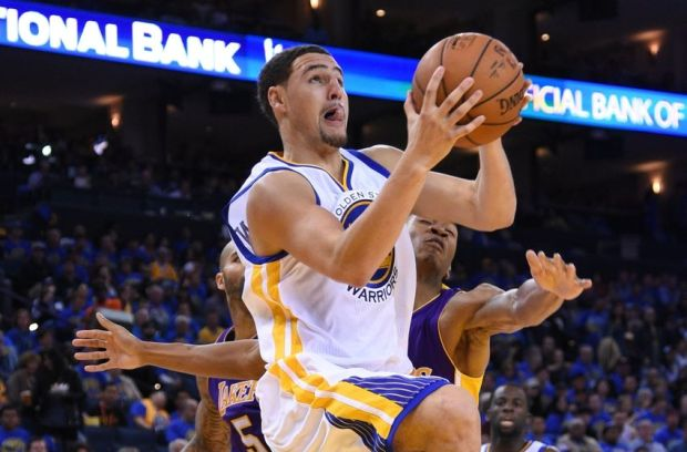 November 1, 2014; Oakland, CA, USA; Golden State Warriors guard Klay Thompson (11, center) drives to the basket against Los Angeles Lakers forward Carlos Boozer (5) and forward Wesley Johnson (11, right) during the third quarter at Oracle Arena. The Warriors defeated the Lakers 127-104. Mandatory Credit: Kyle Terada-USA TODAY Sports