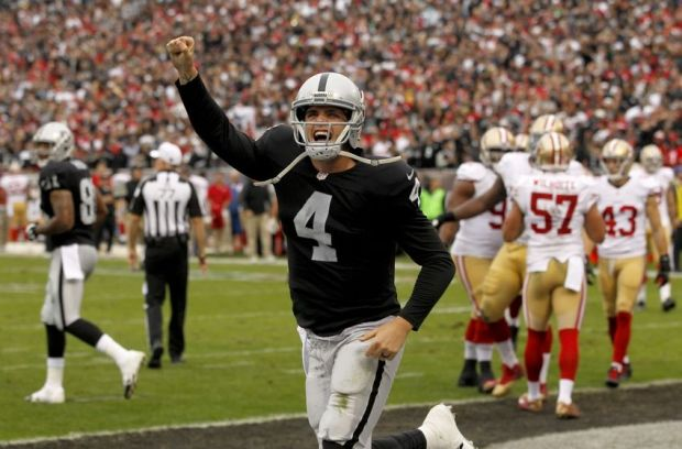 Dec 7, 2014; Oakland, CA, USA; Oakland Raiders quarterback Derek Carr (4) reacts after throwing a touchdown pass against the San Francisco 49ers in the second quarter at O.co Coliseum. Mandatory Credit: Cary Edmondson-USA TODAY Sports
