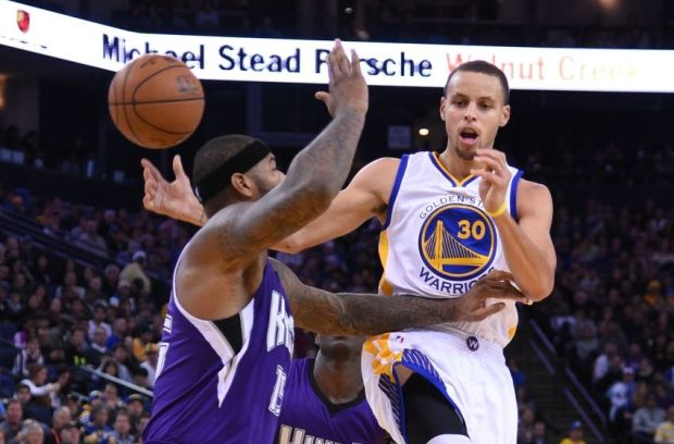 December 22, 2014; Oakland, CA, USA; Golden State Warriors guard Stephen Curry (30) passes the basketball against Sacramento Kings center DeMarcus Cousins (15) during the third quarter at Oracle Arena. The Warriors defeated the Kings 128-108. Mandatory Credit: Kyle Terada-USA TODAY Sports