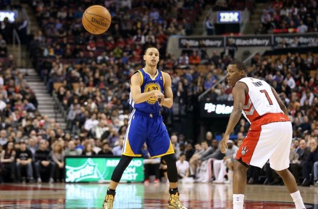 Mar 2, 2014; Toronto, Ontario, CAN; Golden State Warriors point guard Stephen Curry (30) passes the ball as Toronto Raptors point guard Kyle Lowry (7) looks on at Air Canada Centre. The Raptors beat the Warriors 104-98. Mandatory Credit: Tom Szczerbowski-USA TODAY Sports
