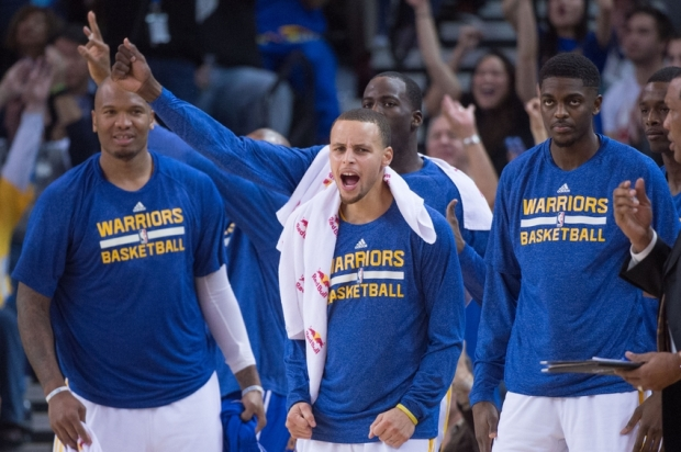 January 7, 2015; Oakland, CA, USA; Golden State Warriors guard Stephen Curry (30, center) celebrates on the bench during the third quarter against the Indiana Pacers at Oracle Arena. The Warriors defeated the Pacers 117-102. Mandatory Credit: Kyle Terada-USA TODAY Sports
