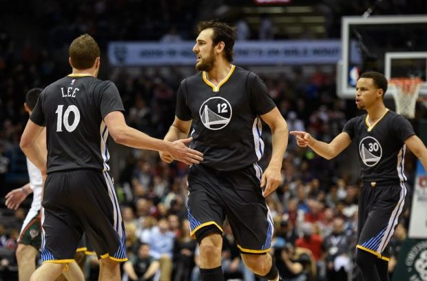 Mar 28, 2015; Milwaukee, WI, USA; Golden State Warriors forward David Lee (10), center Andrew Bogut (12) and guard Stephen Curry (30) react after a Warriors score in the third quarter at BMO Harris Bradley Center. The Warriors beat the Bucks 108-95.  Mandatory Credit: Benny Sieu-USA TODAY Sports