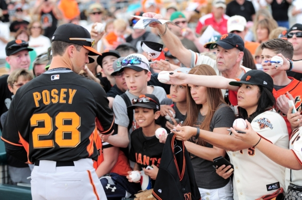Mar 12, 2015; Phoenix, AZ, USA; San Francisco Giants catcher Buster Posey (28) signs autographs for fans prior to a game against the Chicago White Sox at Camelback Ranch. Mandatory Credit: Joe Camporeale-USA TODAY Sports