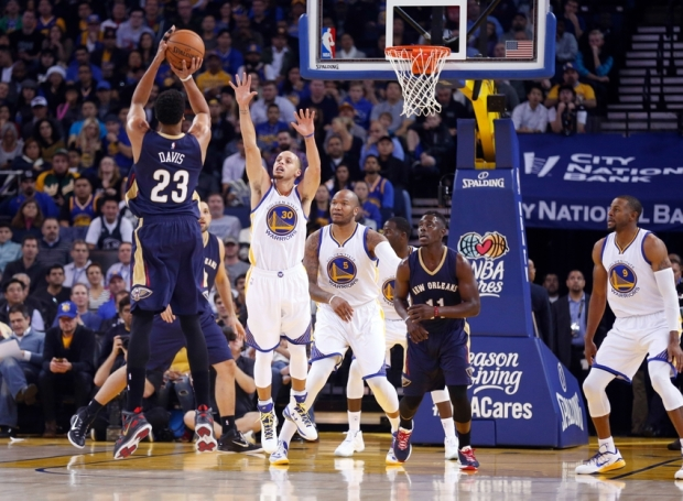 Dec 4, 2014; Oakland, CA, USA; Golden State Warriors guard Stephen Curry (30) defends the shot by New Orleans Pelicans forward Anthony Davis (23) during the first quarter at Oracle Arena. Mandatory Credit: Kelley L Cox-USA TODAY Sports