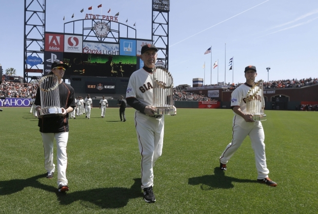 April 13, 2015 San Francisco, USA; San Francisco Giants pitcher Tim Lincecum (left) manager Bruce Bochy (center) and catcher Buster Posey (right) carry the World Series trophies from the 2010, 2012 and 2014 seasons before a baseball game against the Colorado Rockies at AT&T Park. Mandatory Credit: Jeff Chiu-Pool Photo via USA TODAY Sports