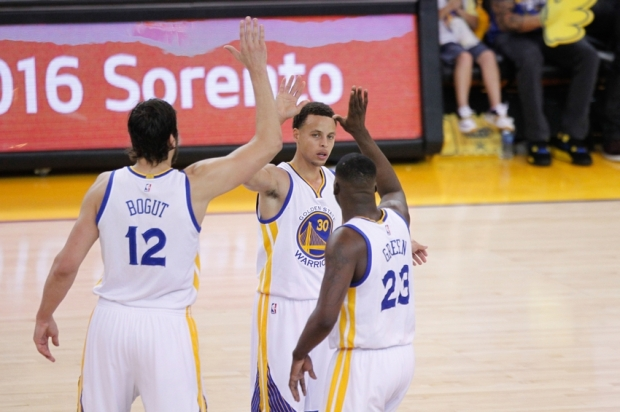 May 3, 2015; Oakland, CA, USA; Golden State Warriors guard Stephen Curry (30) congratulates center Andrew Bogut (12) and forward Draymond Green (23) during a timeout against the Memphis Grizzlies during the third quarter in game one of the second round of the NBA Playoffs at Oracle Arena. The Warriors defeated the Grizzlies 101-86. Mandatory Credit: Cary Edmondson-USA TODAY Sports